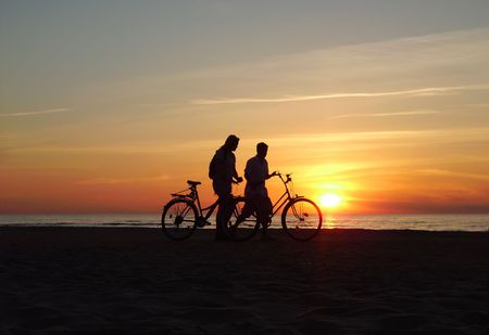 Two bicyclists on a beach