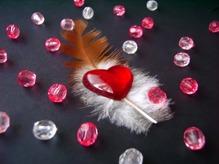 Feather, red heart and beads on black backround Stock Photo