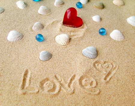 valentine s day beach: Picture of sand, sea shells and red heart Stock Photo