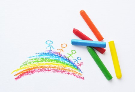 Colorful crayons and kids drawing with rainbow