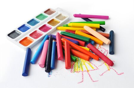 Watercolors and heap of colourfull crayons on white background photo
