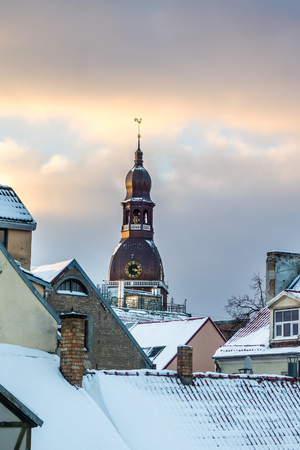 View on Old Riga roofs and Saint Peters Church tower on sunset.