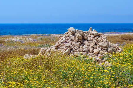 Heap of stones on spring meadow in Paphos Archeological park