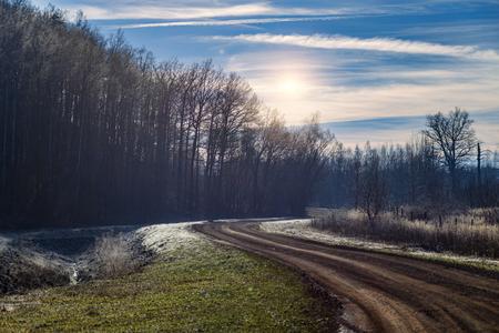 unpaved road in frozen landscape - the sun shining