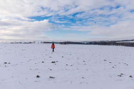 woman hiking over the snowy field alone Standard-Bild