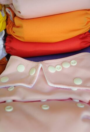 reuseable: Pink cloth diaper in close up with different colored diapers at the background Stock Photo