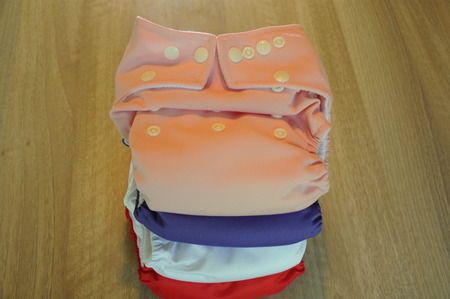 reuseable: girlish cloth diapers with wooden background Stock Photo