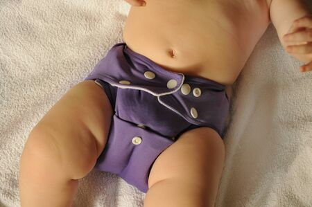 baby with a purple blue cloth diaper on Stock Photo