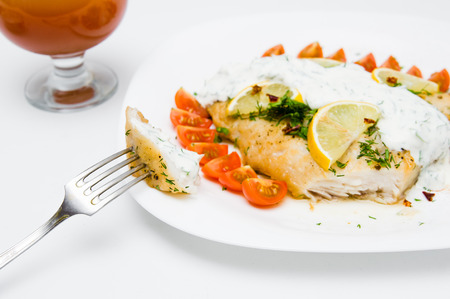 fish sauce: grilled fish with vegetables and cream sauce on white plate