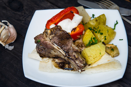 loin chops: lamb loin chops with baked potatoes on wooden table