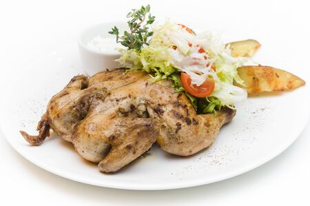 delicious grilled chicken with a side dish of vegetables and herbs on white plate