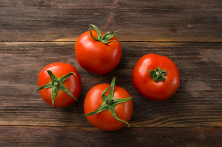 Juicy ripe red tomatoes on a wooden table