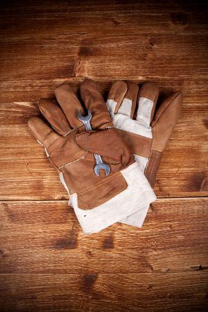 screw key: Two Glove And Screw Key on Vintage Wood Backgorund