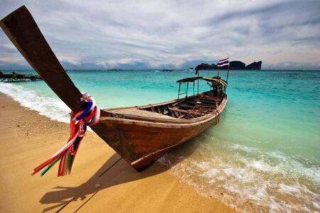Boat near the white sand tropical beach. Andaman sea. Province Krabi. Koh Phi Phi island. Kingdom Thailand