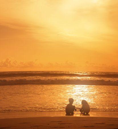 Children play in the rays of the setting sun. Legian. Bali. Indonesia photo
