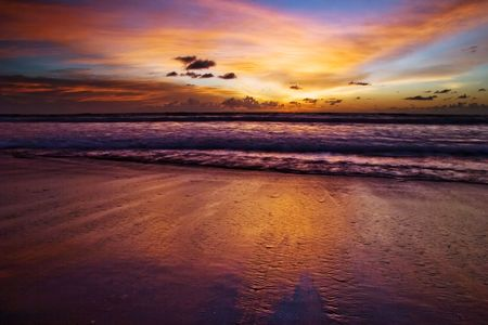 Sunset on the tropical beach. Legian beach on Bali island. Indonesia Stock Photo