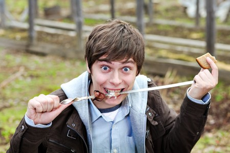 The guy eats meat kebab Stock Photo - 7956539