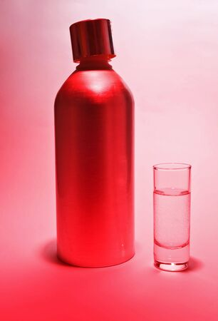 Aluminum bottle and a glass of vodka in pink light  photo