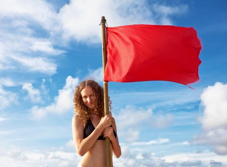 Girl with red flag on blue sky background Stock Photo