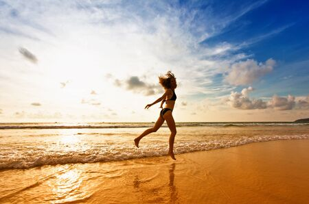 Dancing girl on a tropical beach under the sky at sunset