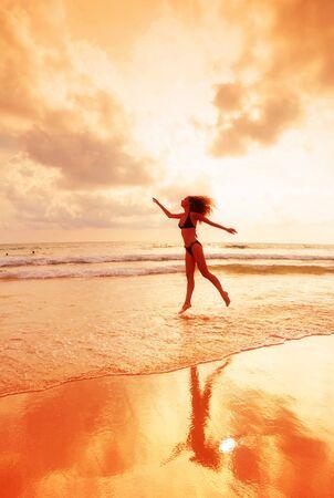 The jumping girl on a tropical beach  photo