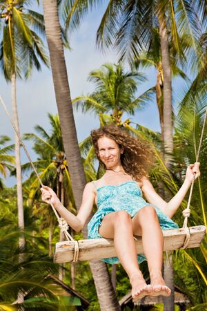 A woman on a swing against the background of palm trees  photo