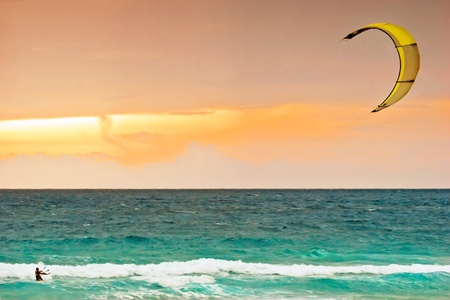 surfing beach: Kite-surfing on orange sunset background .