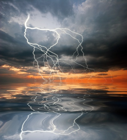 lightning storm: Reflection of lightning and sunset in the water