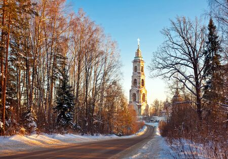 Beautiful winter sunset in the forest and church photo