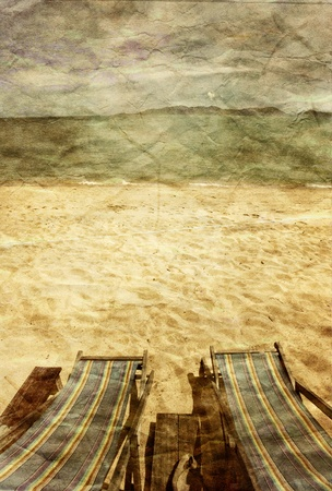 Two sun beach chairs on shore near sea in grunge and retro style  photo