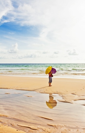 Young woman on the beach in summer under umbrellas photo