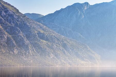 Early misty morning on the beach with sea and mountain views  Kotor bay  Montenegro photo