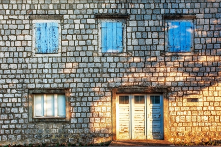 Old stones wall with door and windows in sunset light photo