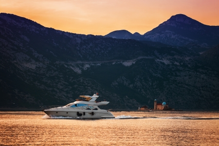 speedboat in the sunset sea on mountains background. Montenegro photo
