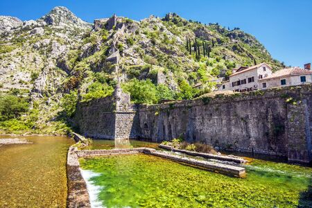 river near the old city on mountains background. Kotor. Montenegro photo