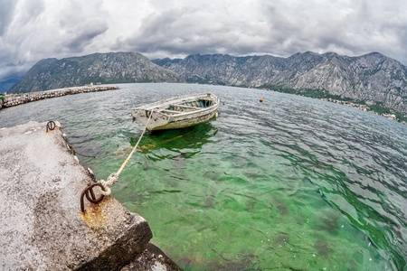 The old boat in the sea with the sea and mountains in gloomy weather. Fisheye view Stock Photo - 16217092