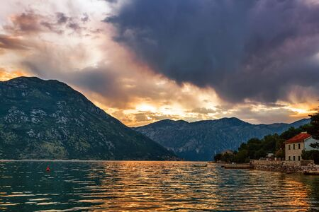 Sunset on the sea with the а foggy mountains. Montenegro photo