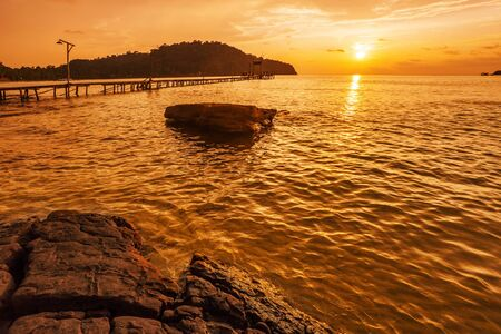 Sunset over the sea. Wooden pier in the sea Stock Photo - 18910807