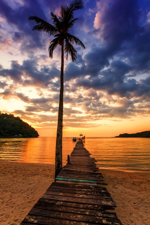 Sunset over the sea. Wooden pier in the sea photo
