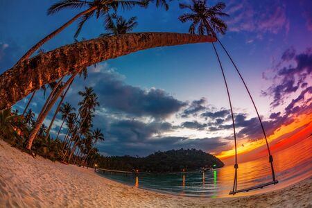 Swing on beautiful sunset at the beach in fisheye view photo