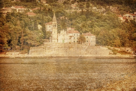 The old church on an island in the sea on moutains background in grunge and retro style Stock Photo - 19324115