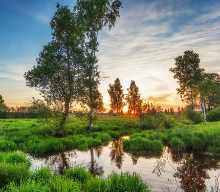 Summer sunset around field with with small river photo