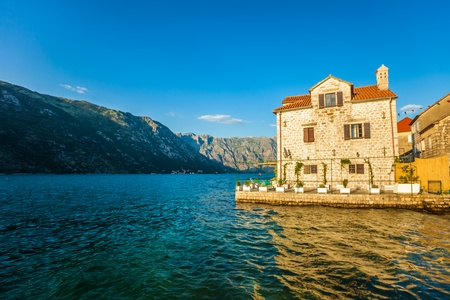 Old house in sunlights at sea on mountains background  Montenegro