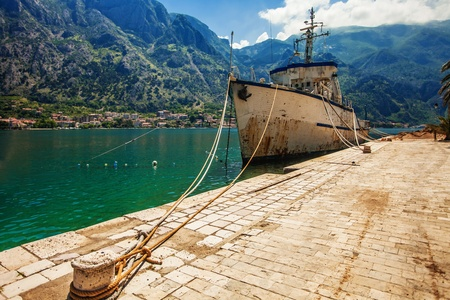 Old fishing ship near the pier at morning on mountains background photo