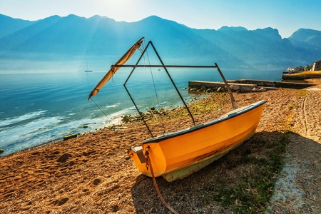 The boat on the beach early in the morning with the sea and mountains in fog photo