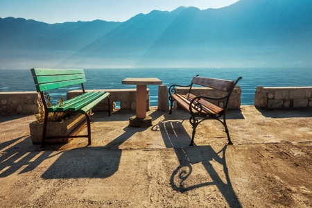 Seafront with benches at morning on foggy mountains background photo