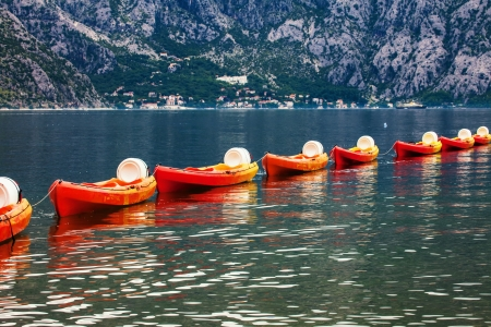 Row of kayaks in the sea on a background of mountains photo