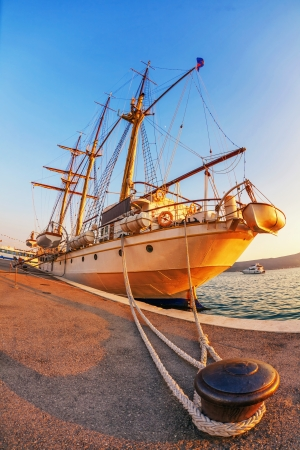 Old sailing ship in the rays of light of the setting sun in the port photo