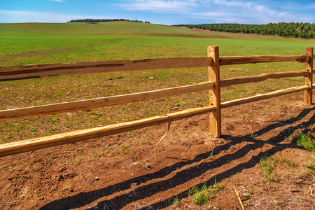 An old wood fence with a green country field behind it photo