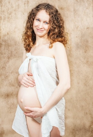 Happy pregnant woman in white shawl on scratch background  photo